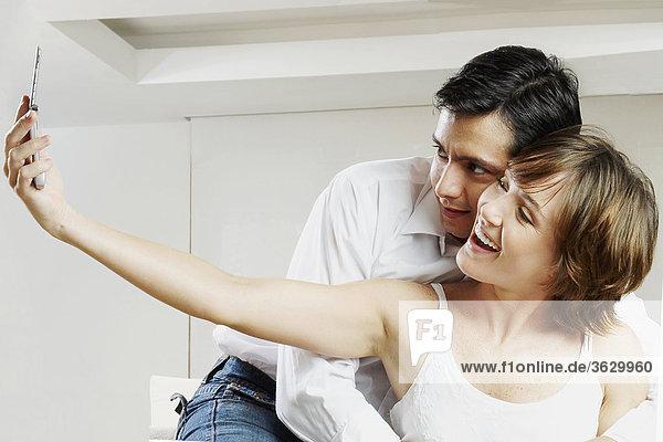 Junge Frau Aufnahme eines Bildes mit einem mittleren erwachsenen Mann umarmen sie von hinten