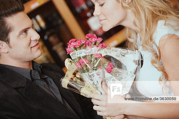 Seitenansicht einer jungen Frau riechen ein Blumenstrauß an ein junger Mann