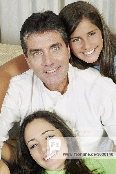 Ein älterer Mann und seine beiden Töchter auf einer Couch sitzen und lächelnd portrait