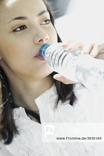 Close-up of a young woman drinking water from a bottle