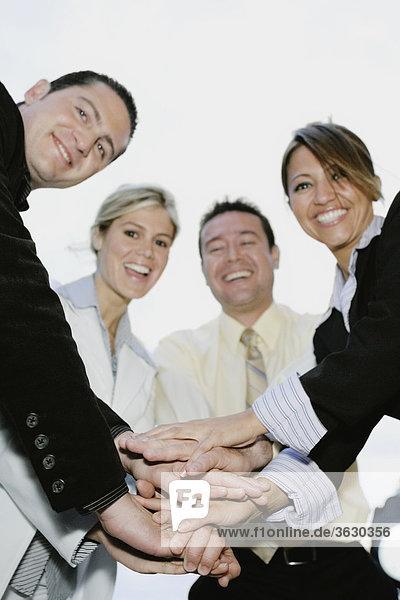 Untersicht zwei Geschäftsleute und zwei Geschäftsfrauen Stapeln Hände