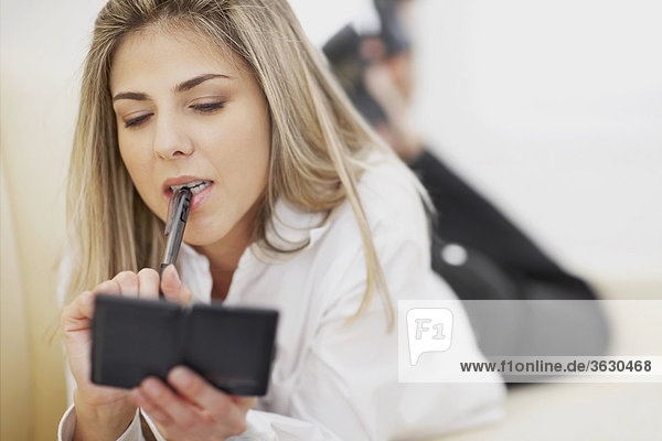 Nahaufnahme einer Mitte erwachsen frau hält einen Stift und einen Taschenrechner