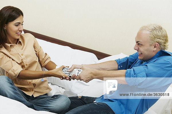Young couple fighting for a remote control on the bed