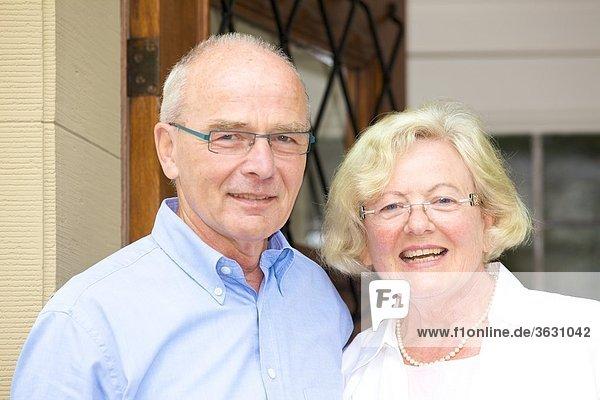 Glückliches Seniorenpaar vor ihrer Haustür  Portrait