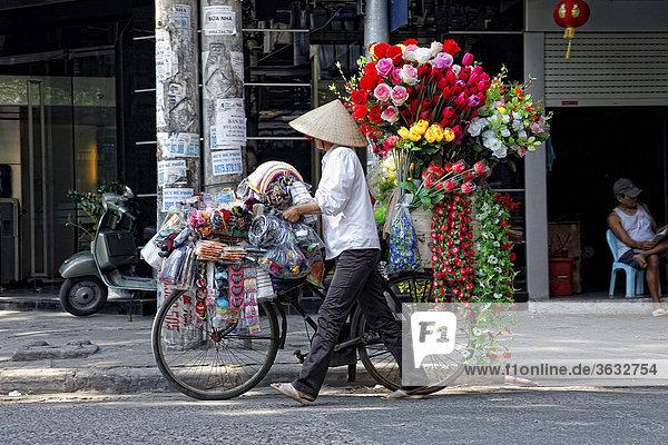 Eine Straßenhändlerin mit ihrem Fahrrad beim Verkaufen ihrer Blumen in Hanoi  Vietnam  Asien