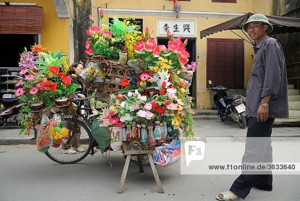 Street vendor selling flowers from his artfully overloaded bicycle in the old quarter of Hoi An  Vietnam
