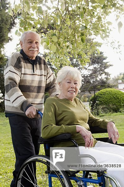 Mann schieben Garten Behinderung Rollstuhl