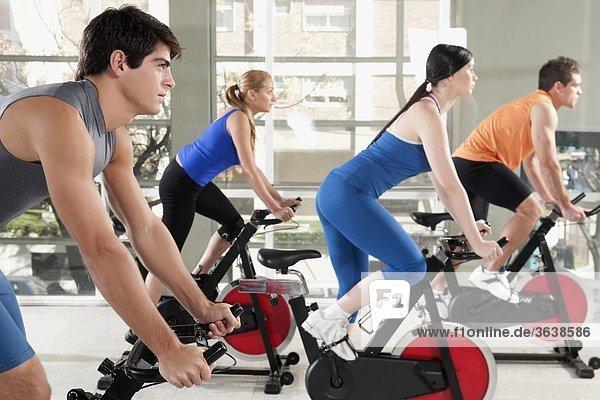 Männer und Frauen auf Ausarbeitung Übungs-Fahrräder in einer Turnhalle