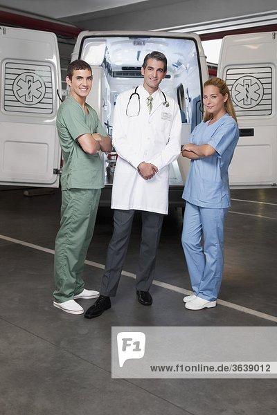 Arzt mit Mitarbeitern vor einen Krankenwagen Stand