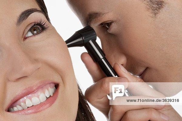Arzt Überprüfung einer Frau Ohr mit einem Otoskop