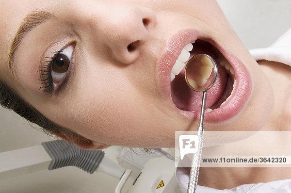 Woman examining ihre Zähne mit abgewinkelter Spiegel