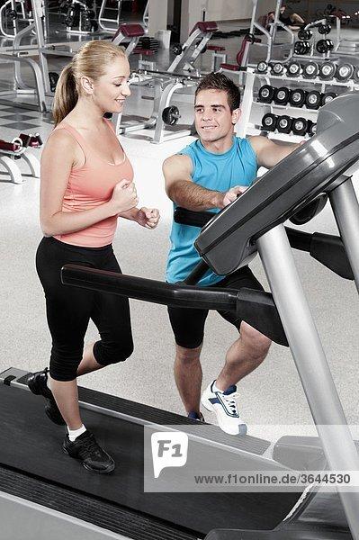 Mann eine Frau auf einem Laufband Unterstützung