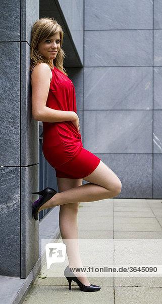 Junge Frau in rotem Kleid und hochhackigen schwarzen Schuhen lehnt an Wand