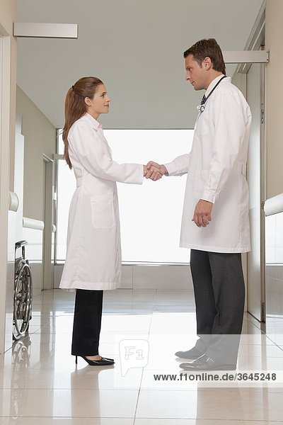 Two doctors shaking hands in a hospital corridor