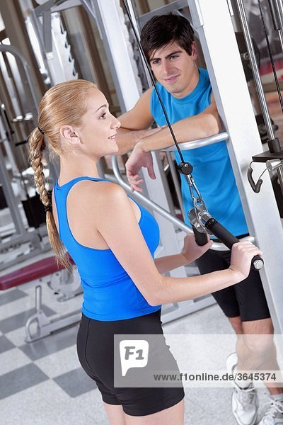 Frau beim training in einer Turnhalle mit einem Mann neben ihr stehen
