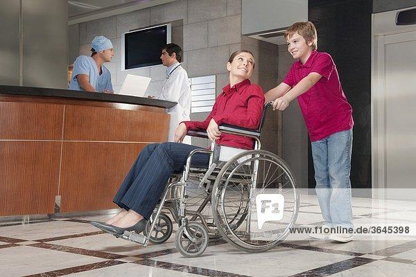 Frau sitzen im Rollstuhl geschoben von ihrem Sohn
