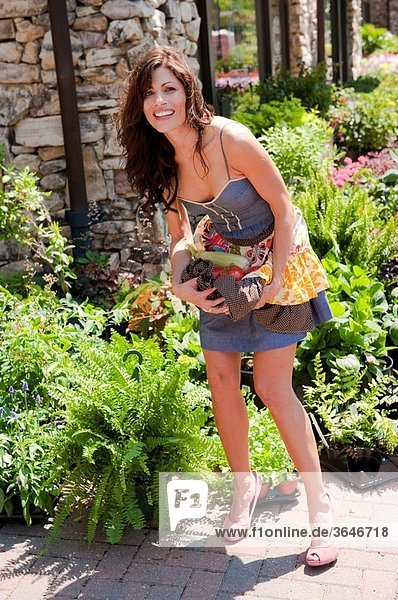 32 year old brunette woman in summer dress at an outdoors garden market holding vegetables in her apron.