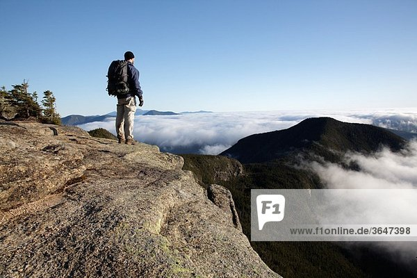 A hiker takes in the view of undercast from the summit of Mount Osceola in the White Mountains  New Hampshire USA