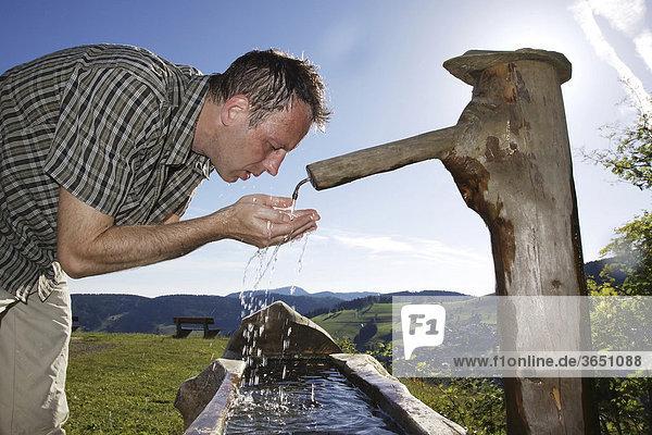 Ein Mann  Mitte 40  kühlt sich an einem Brunnen ab  bei Todtnauberg im Schwarzwald  Baden-Württemberg  Deutschland  Europa Ein Mann, Mitte 40, kühlt sich an einem Brunnen ab, bei Todtnauberg im Schwarzwald, Baden-Württemberg, Deutschland, Europa