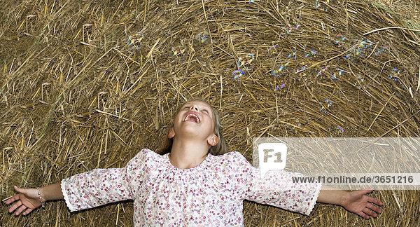 8-jähriges Mädchen streckt die Arme aus und beobachtet Seifenblasen über ihr