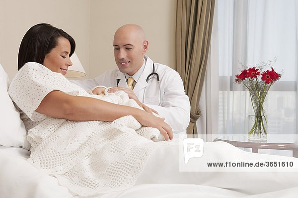 Arzt mit einer Frau mit ihrem Neugeborenes Baby in einem Krankenhaus
