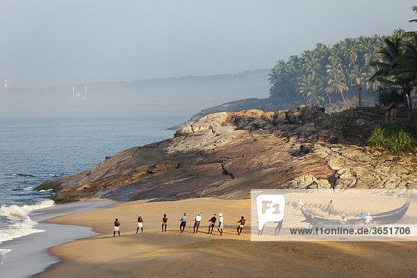 Fischer ziehen Netz ein,  Strand südlich von Kovalam,  hinten Vizhinjam,  Malabarküste,  Malabar,  Kerala,  Südindien,  Indien,  Asien