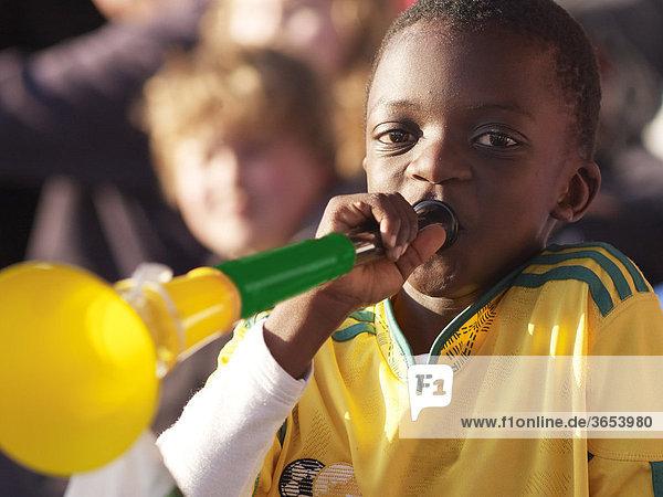 Südafrikanischer Junge im Fußballnationaltrikot Südafrikas posaunt in eine Vuvuzela