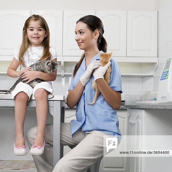 Weibliche Vet mit einem Mädchen tragen Katzen