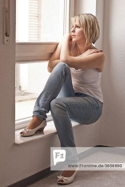 Junge Frau sitzt an einem Fenster