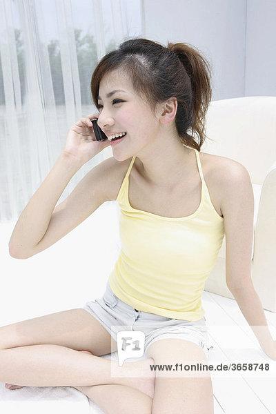 Junge Asiatin am Telefon
