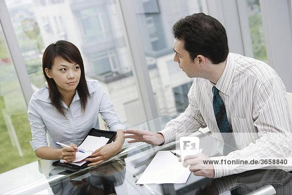 Eine Frau und ein Mann sprechen im Büro