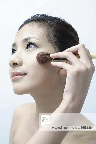 Young Asian woman putting on make-up