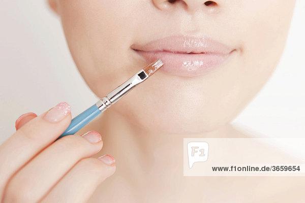 Junge Frau wird geschminkt  Lipgloss mund