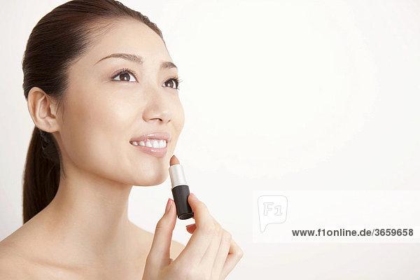 Junge Frau trägt Lippenstift auf mund