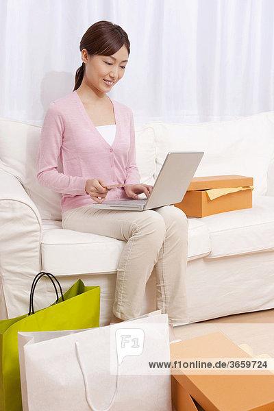 Junge Frau sitzt auf dem Sofa  Online-Shopping