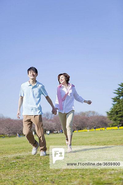 Junges Paar läuft Hand in Hand