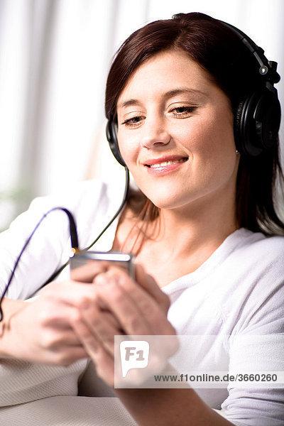 Junge Frau hört Musik über Kopfhörer im Wohnzimmer