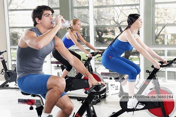 Mann Trinkwasser mit zwei Frauen aus in ein Fitness-Studio