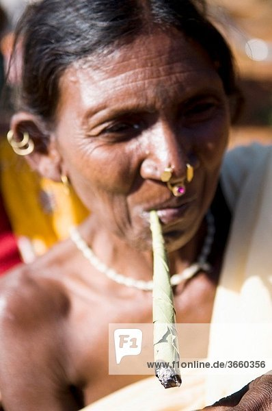A tribal woman from Orissa smoking a traditional rolled cigarette.