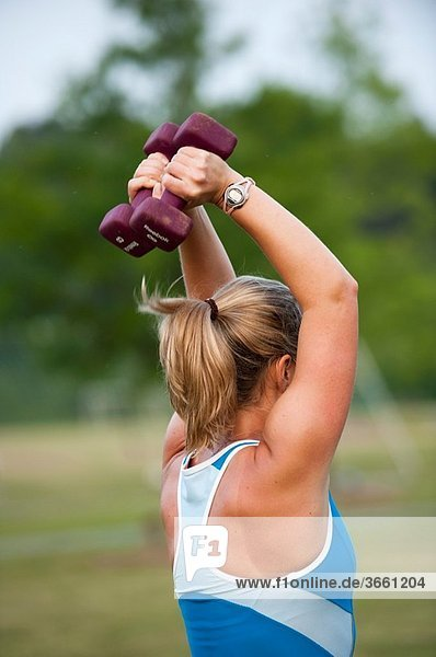 Back view of a woman in workout clothes holding a dumbbell above her head at a boot camp with other other women in the background.