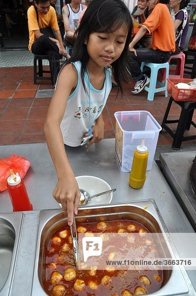 Malacca (Malaysia): a girl serving ´fish balls´ in a Chinatown´s street stall