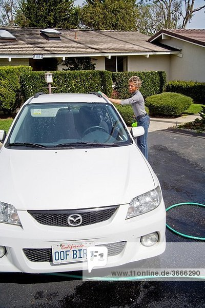 Using a bucket of detergent and a garden hose  an adult woman washes her car with a sponge outdoors in Laguna Niguel  California