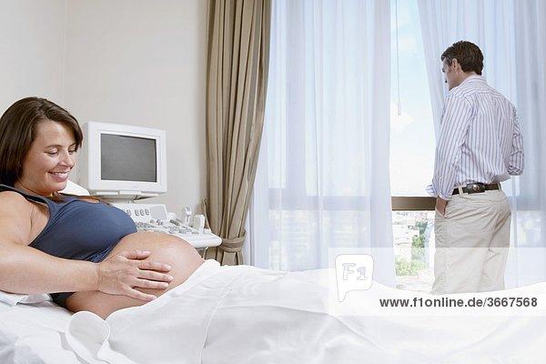 Schwangere Frau in einem Krankenhaus mit ihrem Ehemann Blick durch ein Fenster