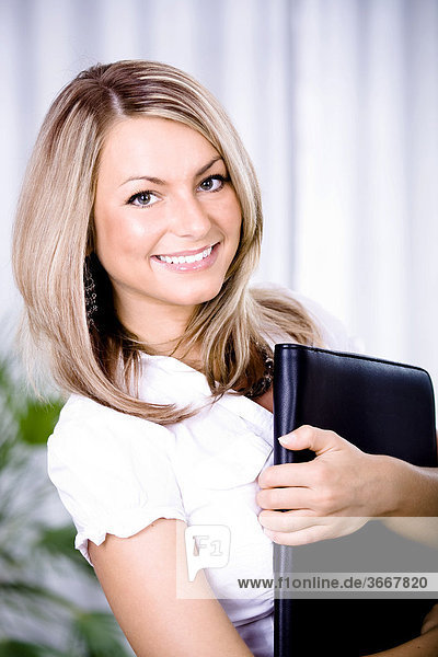 Junge Frau mit Mappe im Büro
