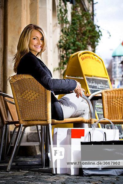 Junge Frau beim Shopping macht Pause im Straßencafe