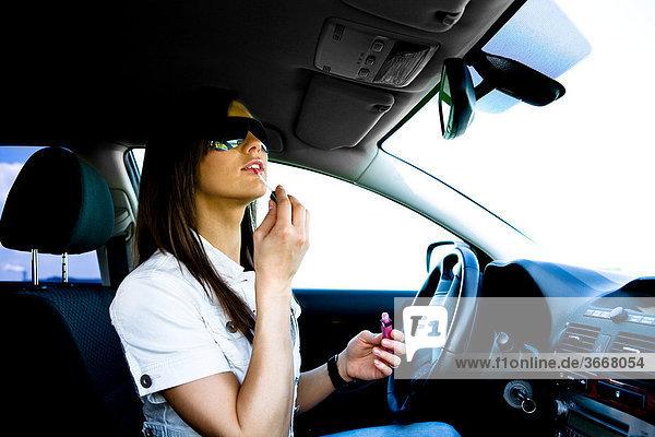 Junge Frau schminkt sich im Auto