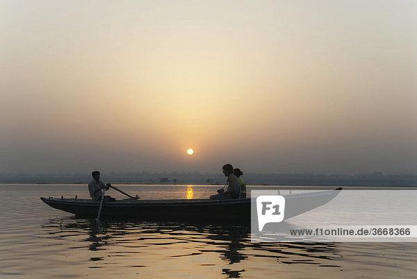 Paar auf Boot blickt in Sonnenaufgang  Ganges  Varanasi  Indien  Asien