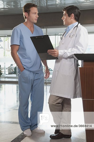 Doctor discussing with a male nurse discussing