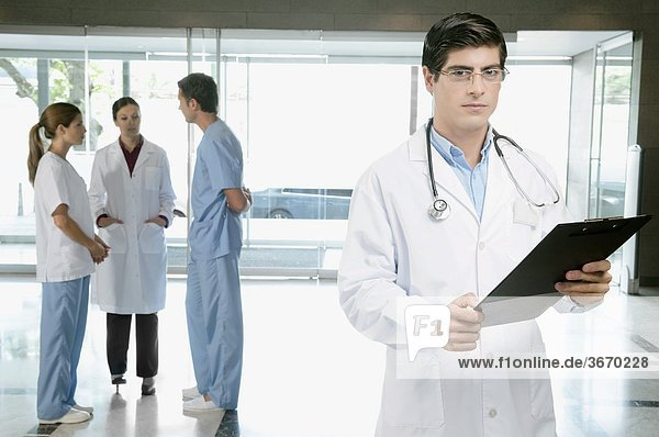 Doctor holding a clipboard with his colleagues discussing in the background