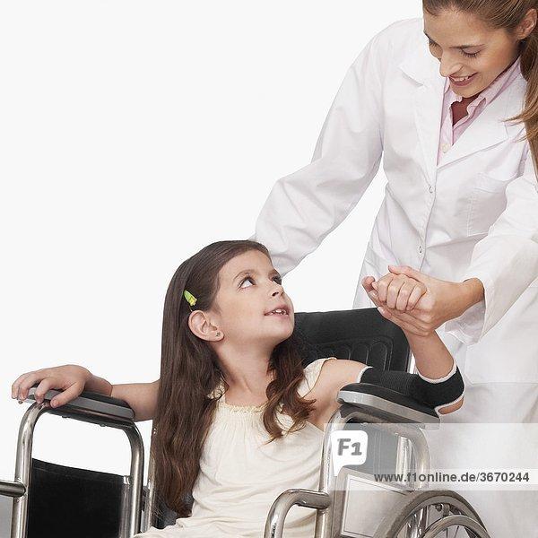 Ärztin mit einem Patienten im Rollstuhl